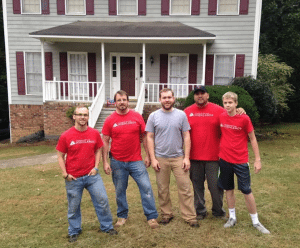 <em>Volunteer Alan Cook (second from right) with his son John (far right) and other First Saturday team members after working in a yard and doing home repair.</em>