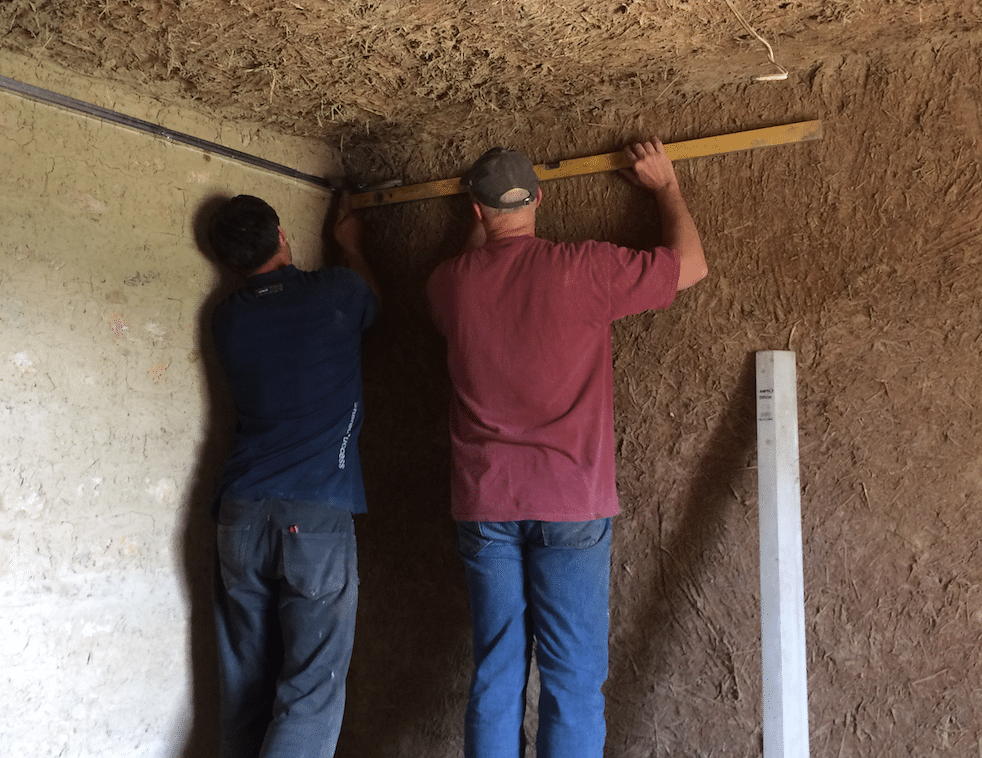 <em>Team member David Brown works with Andrae from Moldova to measure and attach braces for hanging sheetrock in a mud-thatch house.</em>
