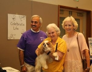"""<em> St. Vincent's Birmingham Oncology Counselor Louis Josof with Hand in Paw Volunteer Phillipa Bainbridge, Breast Cancer Survivor Jewel Redman and Hand in Paw dog """"Pippa"""" at the St. Vincent's National Cancer Survivors Day event. Pippa often comes to St. Vincent's to visit with cancer patients and staff.</em>"""