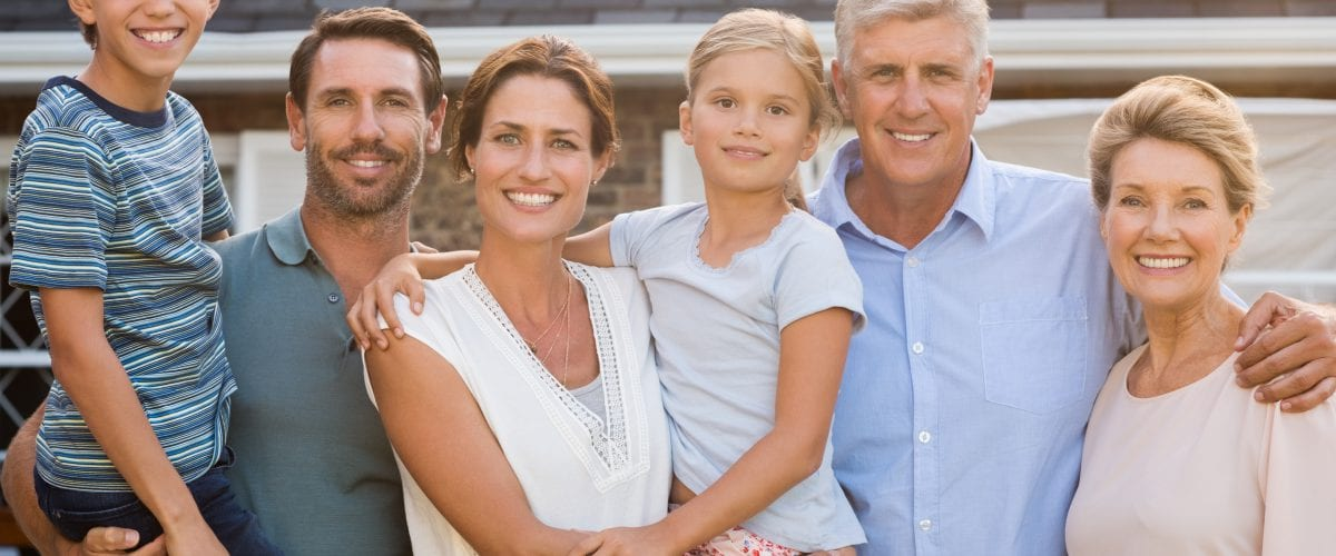 Portrait of cheerful extended family standing outside their house. Happy family standing outside and looking at camera. Parents with grandparents e children enjoying vacation together.