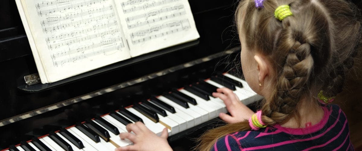 child plays on piano lesson of the music