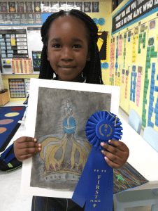 <em>Our Lady of Sorrows Catholic School 1st-grader Addison Jackson proudly displays her artwork of Our Lady of Fatima's Crown and her blue ribbon for placing first in the Homewood Library's Student Juried Art Contest.</em>