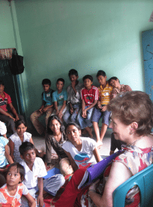 <em>Gloria Whitlock shows children living in India a picture book of salvation.</em>