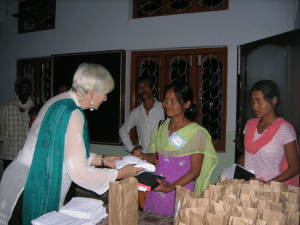 <em>Margaret O'Kelley distributes Assamese Bibles at a conference in India.</em>