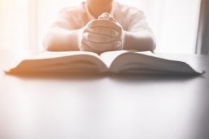 bigstock Man Praying On Holy Bible In T 226266571