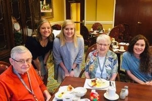 Senior Scene Brookdale 2 female students standing next to table with residents