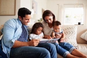 Family of four on a couch reading a book together.