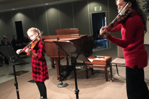Student and teacher playing the violin